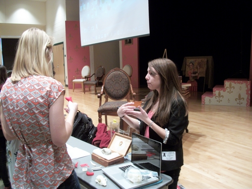 Mariana Zechini discusses a plastic replica of an artifact with a Clover Hill High School student.