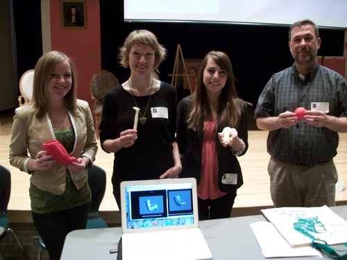 Virtual Curation Laboratory team members hold plastic replicas of artifacts created from scanned digital models.  From left to right are Ashley McCuistion, Crystal Castleberry, Mariana Zechini, and Dr. Bernard K. Means