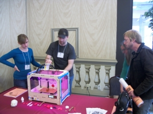Makerbot in action with Rachael (left) and Allen (center). Brian Schools of CRI looks on.