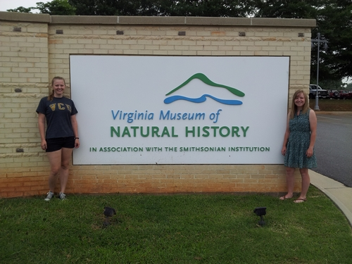 Lauren and Ashley stand on either side of the VMNH sign.