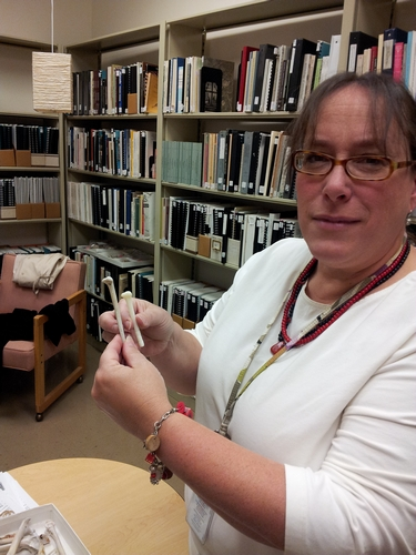 Dr. Moore holds a right turkey radius and replica made into bead stock.