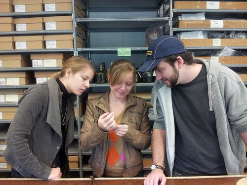 Olivia, Ashley, and Allen examine an artifact from CWF.