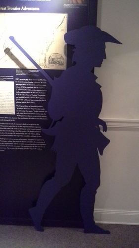 Wooden cutout of George Washington with a gun.