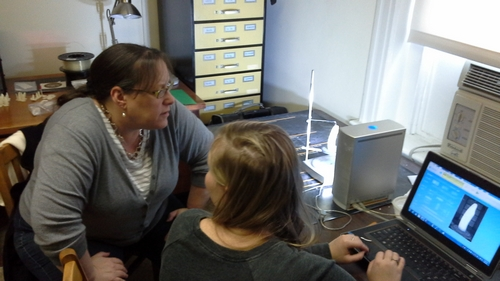 Lauren Volkers shows Dr. Moore how we scan artifacts using a carved hippopotamus tooth.