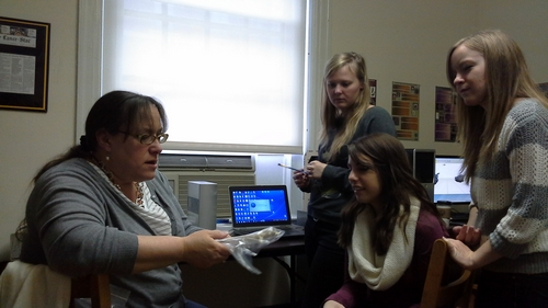 Dr. Moore, left, speaks with students in the Virtual Curation Laboratory.