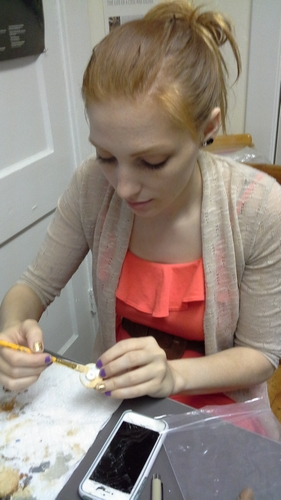Intern Beck Bowman paints replica artifacts for future display in the DC Public Library