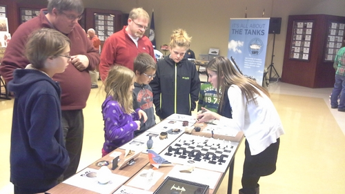 Chelsea Miller discusses Jamestown archaeology with a young visitor who had recently been at Jamestown.