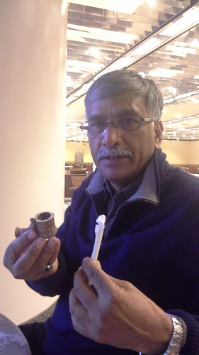 Dr. Vinod Nautiyal holds a 3D printed Civil War pipe and a passenger pigeon bone printed at 300 % of actual size.