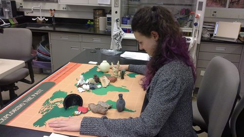 Brenna Geraghty contemplates the artifacts selected for the world of archaeology panel