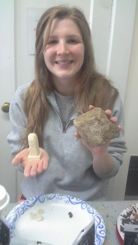 Zoe Rahsman holds a fragment of Aquia sandstone adjacent to the 3D model.