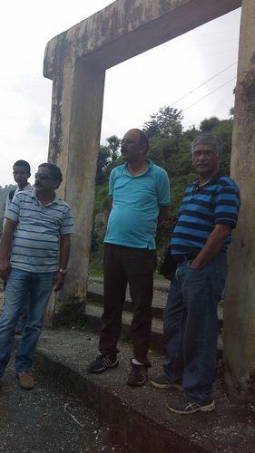 Praadeep Saklani, R. C. Bhatt, and Vinod Nautiyal stand near the entrance to the small town.