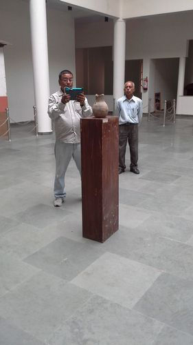 Sudhir scans a vessel while the museum security guard watches.