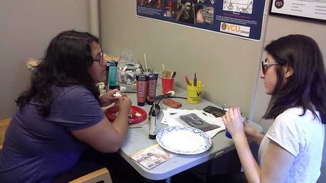Lucia Aguilar (left) tells Bike Race student Taylor Conrad how to 3D scan artifacts.