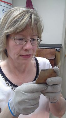 George Washington's Ferry Farm's Small Finds analyst Laura Galke examines a colonoware bowl fragment.