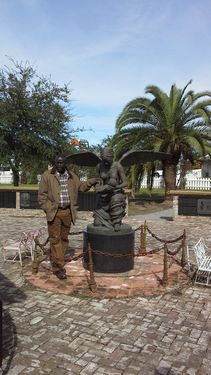 Dr. Ibrahima Seck stands next to the sculpture of the angel carrying the dead child to Heaven.