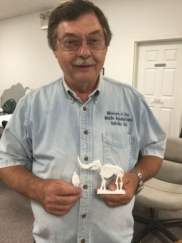 Butch Surber holds a replica of VCU student Lisa Day scaled to the size of the replica mastodon that he is holding.